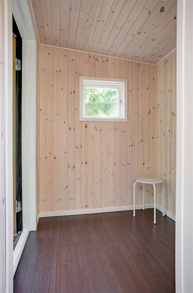 Välkommen in! Liten entréhall med panel på vägg.