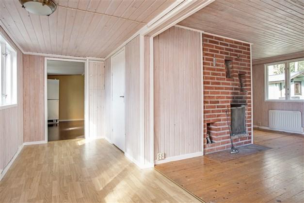 Hall med portal mot vardagsrum, ingång till dusch/wc och kök.