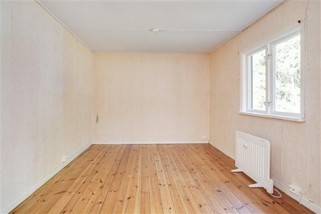 Sovrum med fint trägolv och fönster ut mot baksidan.