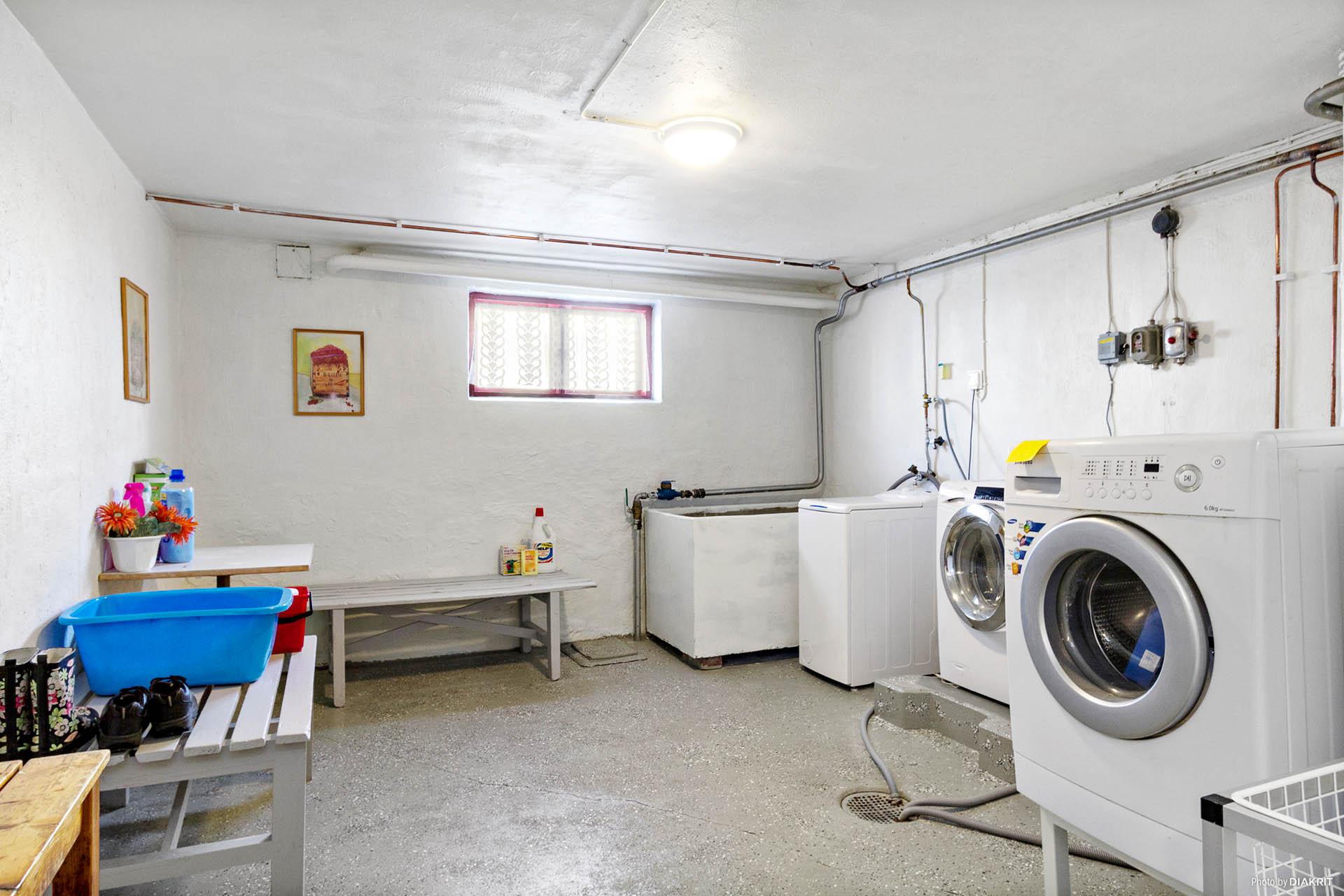 Tvättstuga med egna tvättmaskiner. Tvättmaskinen närmast i bild tillhör lägenheten.