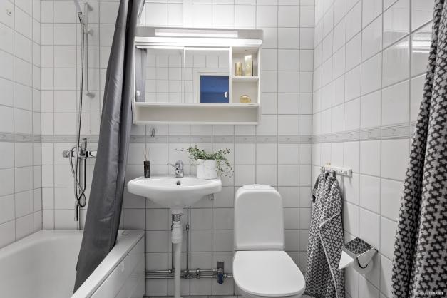 Badrum med kaklade väggar och klinkergolv.