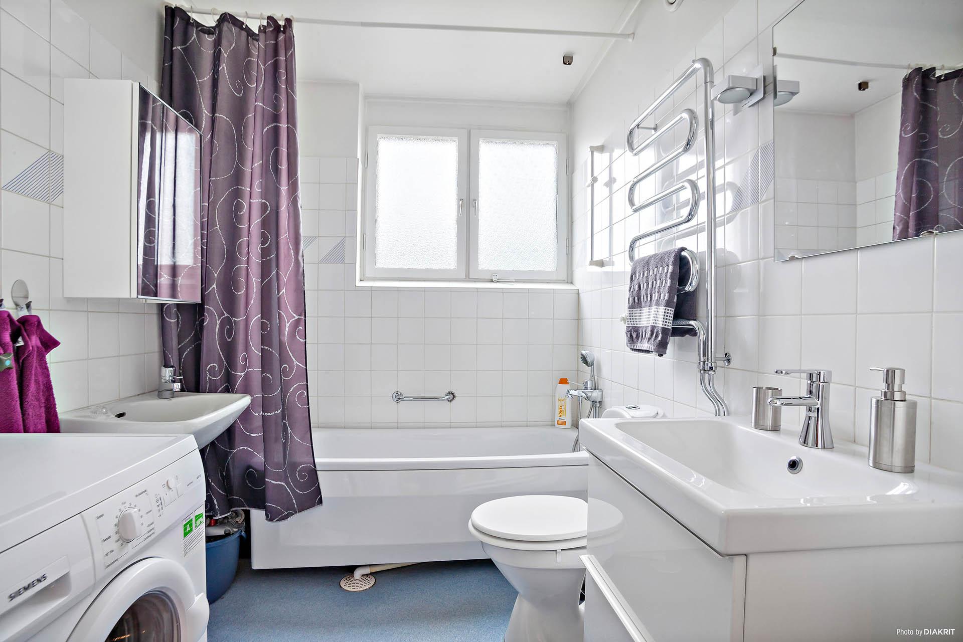 Badrum utrustat med torkskåp, tvättmaskin, dubbla handfat och badkar.