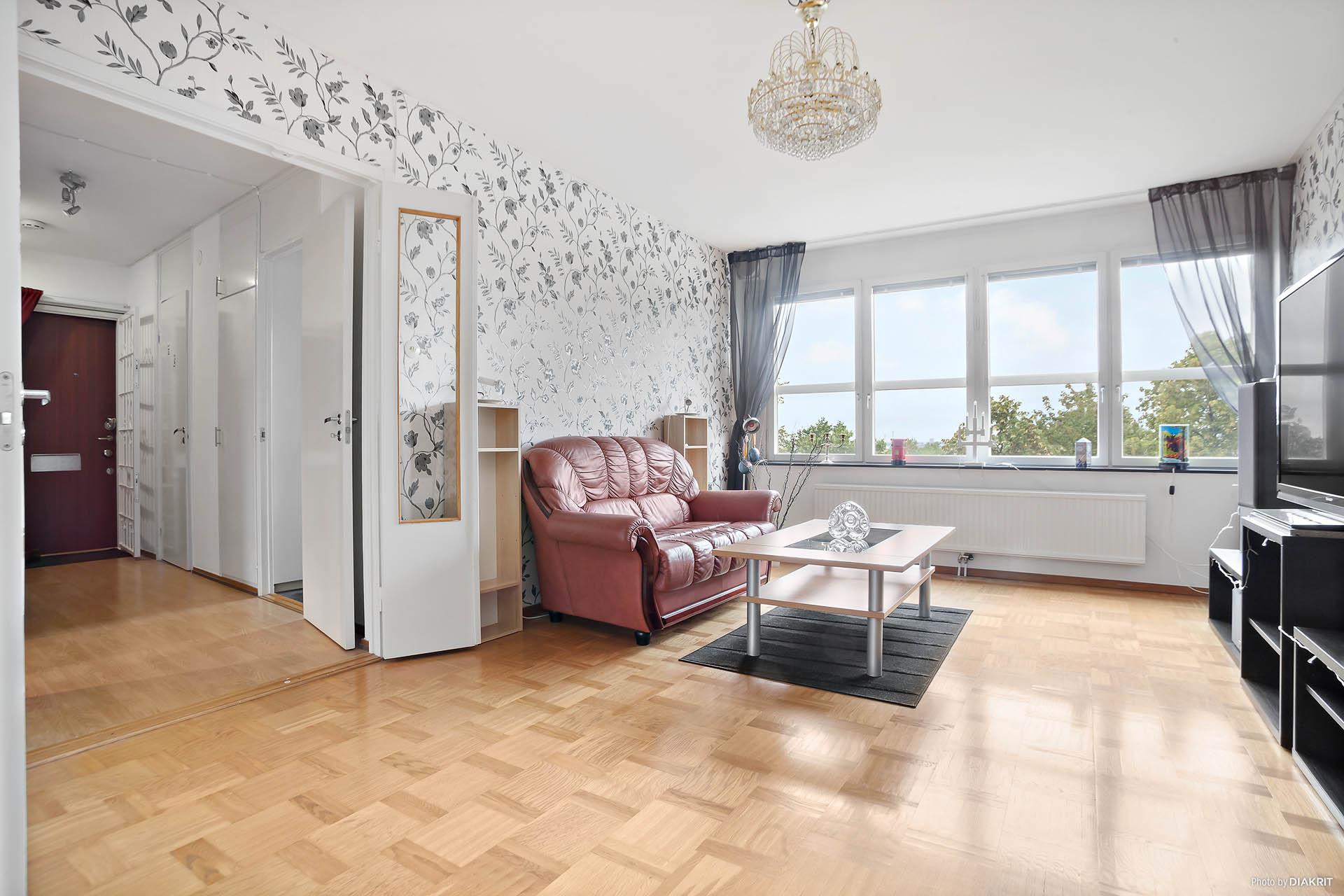 Stort och lättmöblerat vardagsrum med stora fönsterpartier mot nedanförliggande innerstaden.