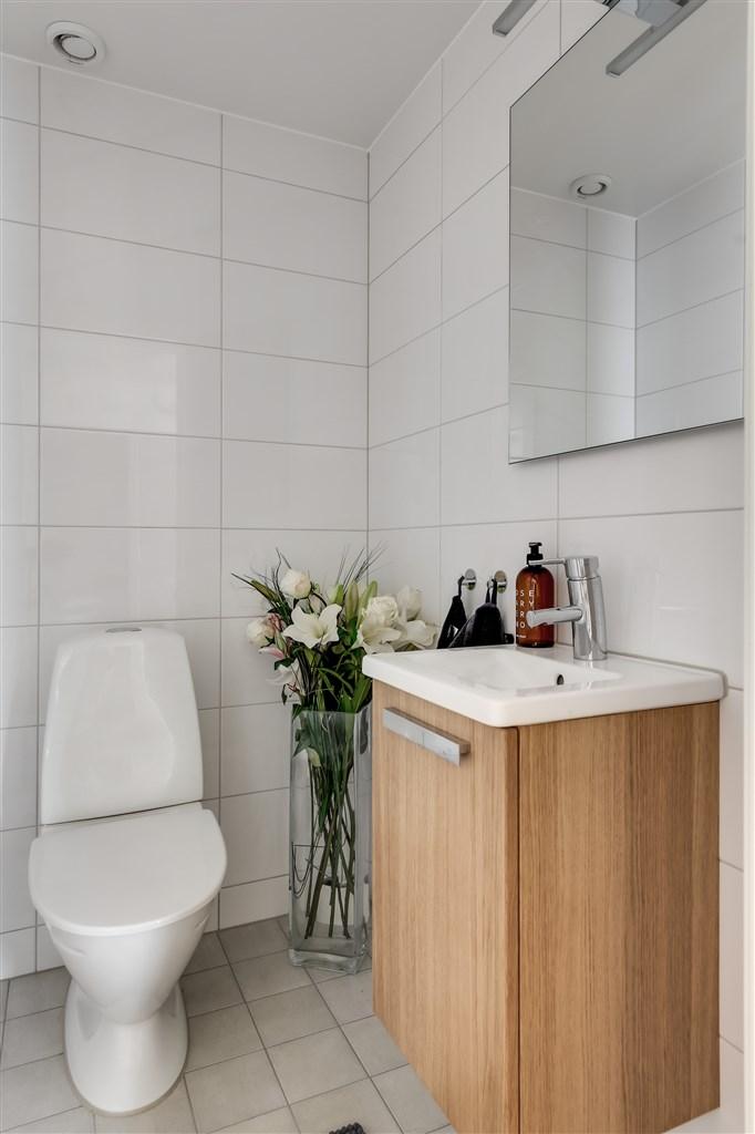 Ljus och fräsch gästwc med helkaklade väggar och klinker på golvet, toalett och handfat.