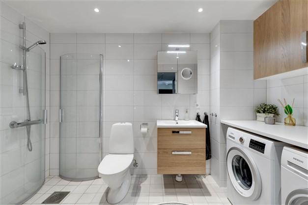 Badrummet är smakfullt och stilrent inrett med dusch och duschdörrar i glas, nedsänkt tak med infällda spotlights.