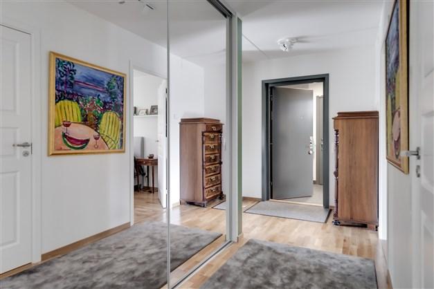 Entré/hall som är inredd med inbyggd garderob med skjutdörrar.
