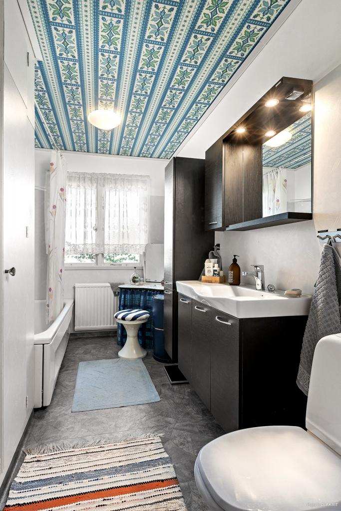 Renoverat badrum med häftig tapet i tak