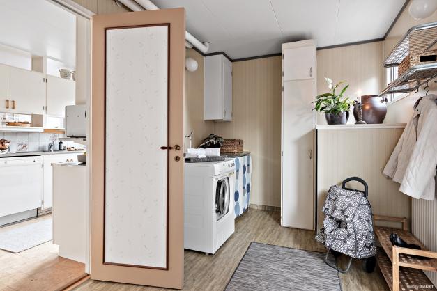 Vidare in från köket når man tvättstugan och förrådet. I tvättstugan finns även en groventré som man når från husets gavelsida.
