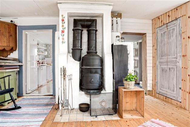 I Rummet som har ingång både från kök och hall finns värmande Bergslagskamin.