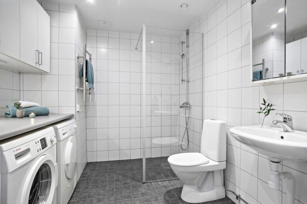 Välutrustat badrum med tvättmaskin och torktumlare
