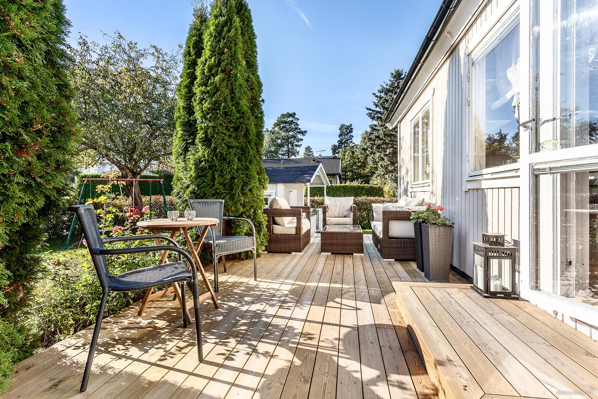 Stor träbelagd altan med gott om plats för loungedel