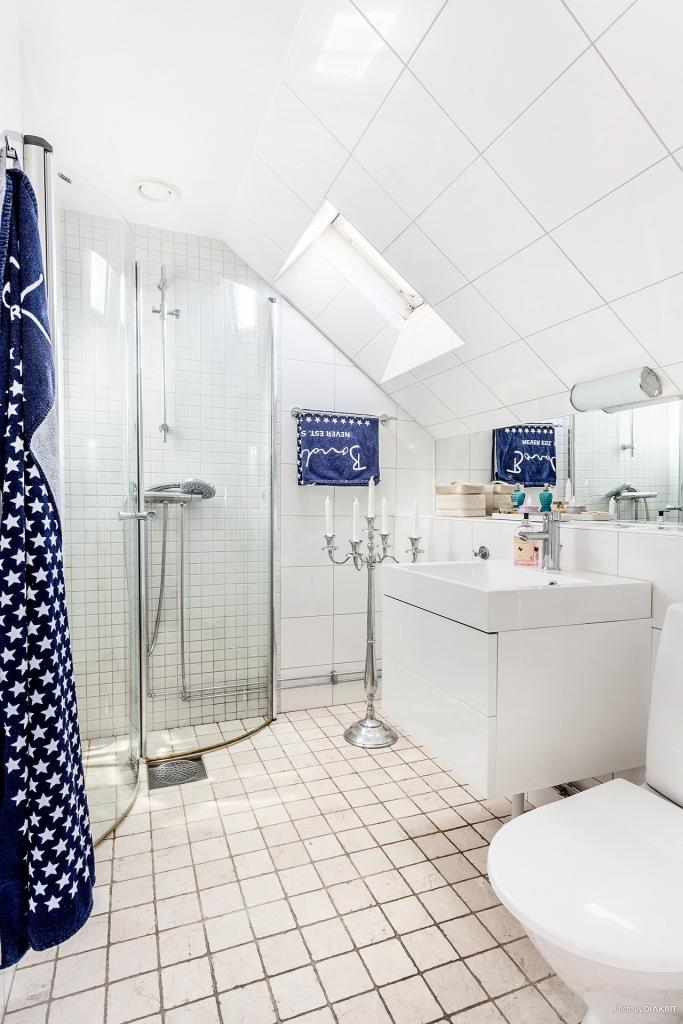 Helkaklat ljust badrum med duschhörna