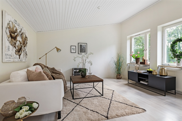 Vardagsrummet med fönster mot trädgård och naturreservat