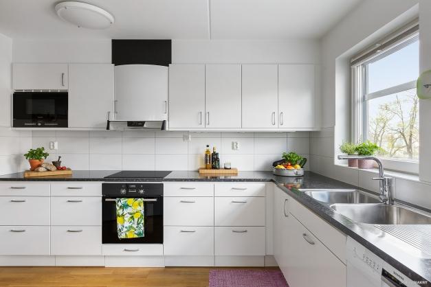 Fint kök i vinkel med mycket förvaringsyta, praktiska sockellådor och trevlig utsikt genom fönstret.