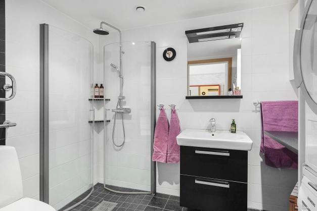 Badrummet är helkaklat med ljust kakel som bryter av mot mörkt klinker. Här finns både golvvärme, spotlights och separat tvättavdelning med praktisk bänksskiva under överskåp.