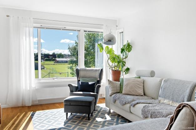 Vardagsrum med stort fönsterparti.
