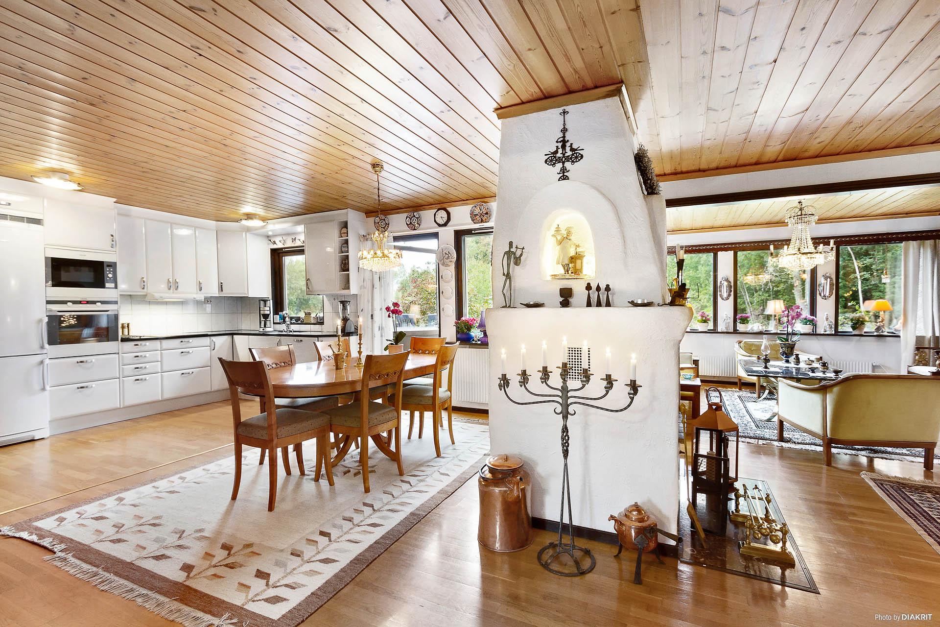 Kök och vardagsrum i öppen planlösning och öppen spis centralt placerad.