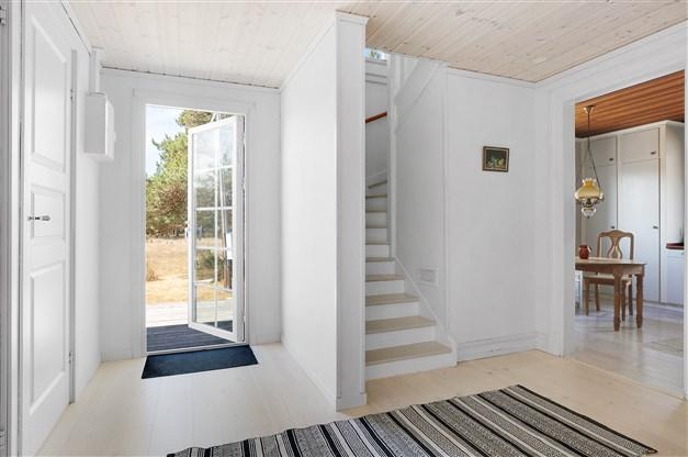 Hall med trappa till övervåningen och utgång till trälagd altan