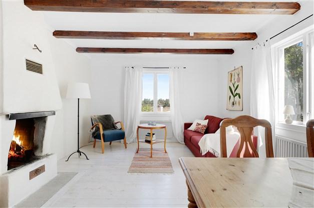 Vardagsrum med öppen spis och synliga takbjälkar
