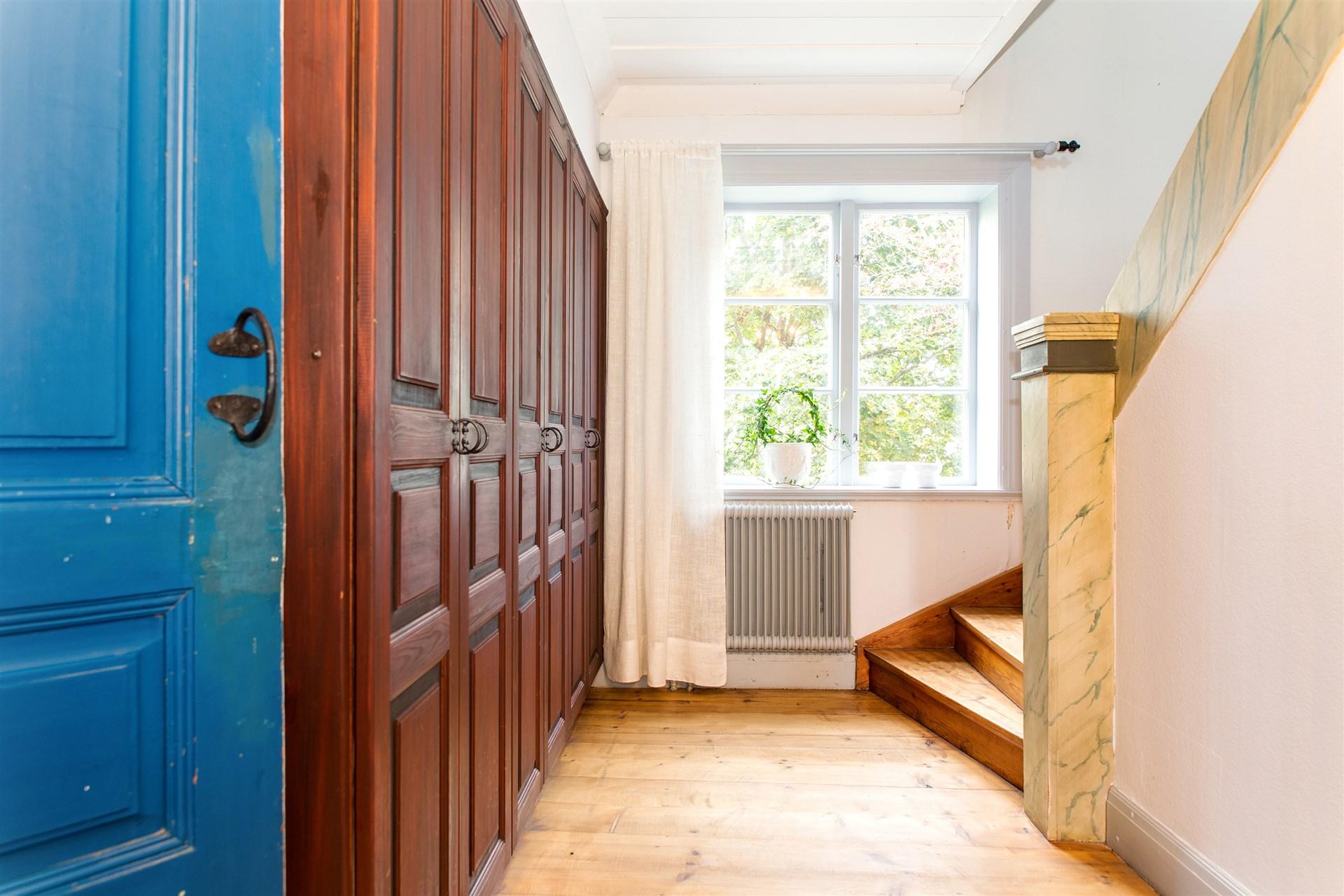 Hall med gott om garderober och  trappa upp till övervåningen
