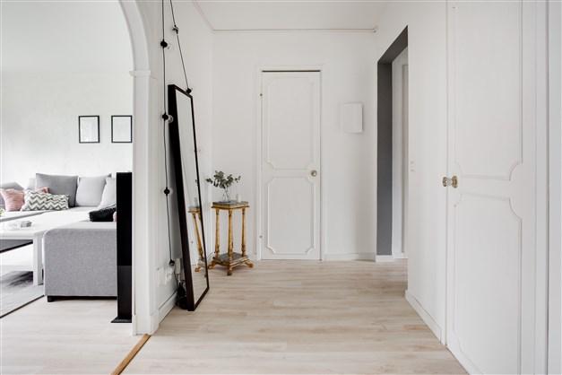 Stor och ljus hall med klädkammare och portal mot varadagsrummet.