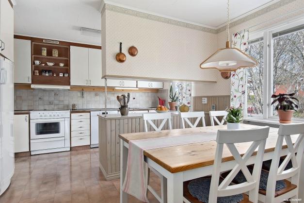 Kök med bra förvaringslösningar och plats för matbord vid fönster.