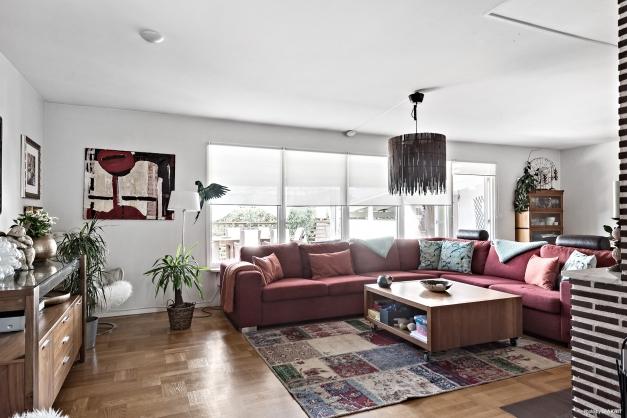 Vardagsrummet har plats för rejäl soffgrupp. Vacker parkett på golvet. En öppen spis är centralt belägen i rummet.