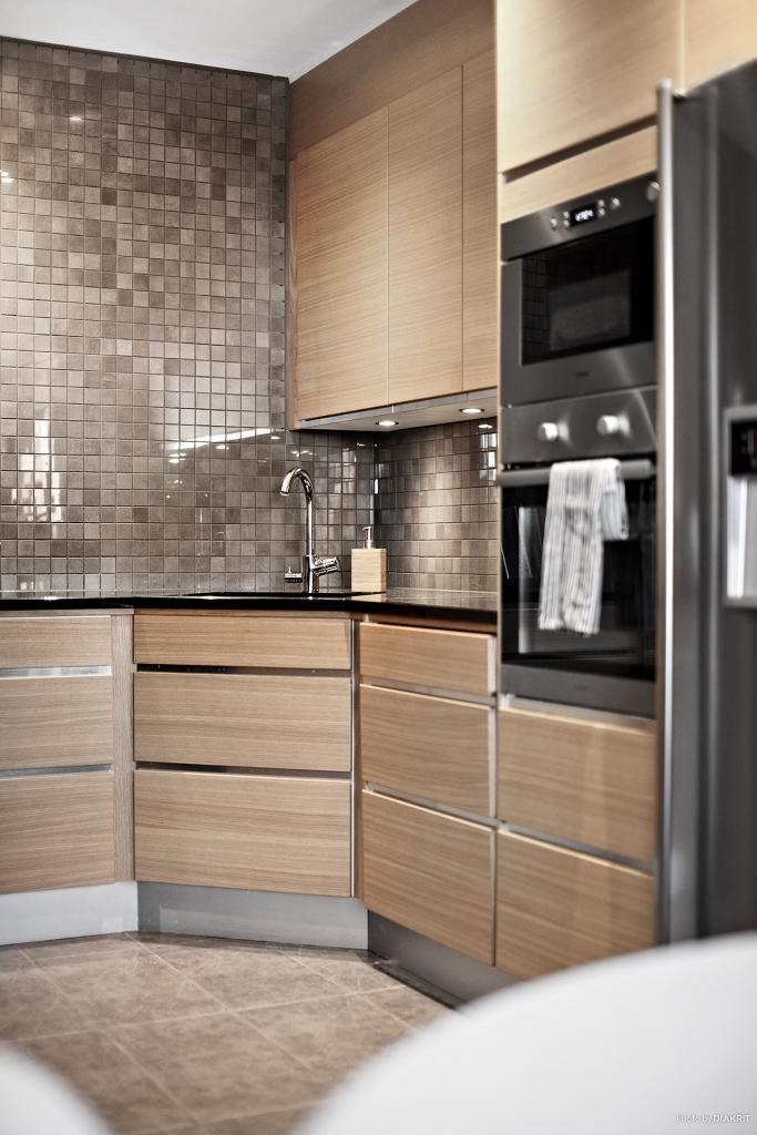 Köket, kakel i grå ton som går fint ihop med golvet av klinker.