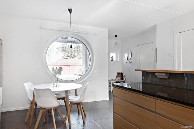 Matplatsen i köket ramas in av det stora runda karakteristika fönstret.