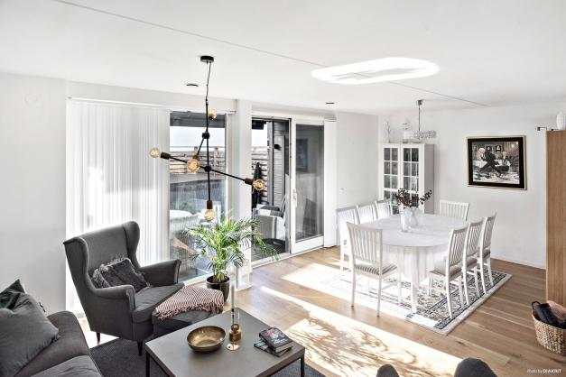 Vardagsrummet och matrummet har stora fönster och skjutdörrspartier mot uteplatsen och trädgårdstäppan