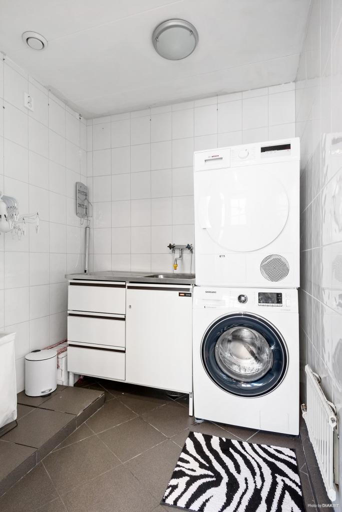 Helkaklad tvättstuga med tvättmaskin, torktumlare och tvättställ.