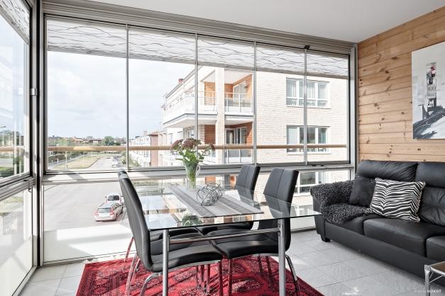 Inglasad balkong i västerläge med klinkergolv, stilfull träpanel på väggen och plissegardiner.