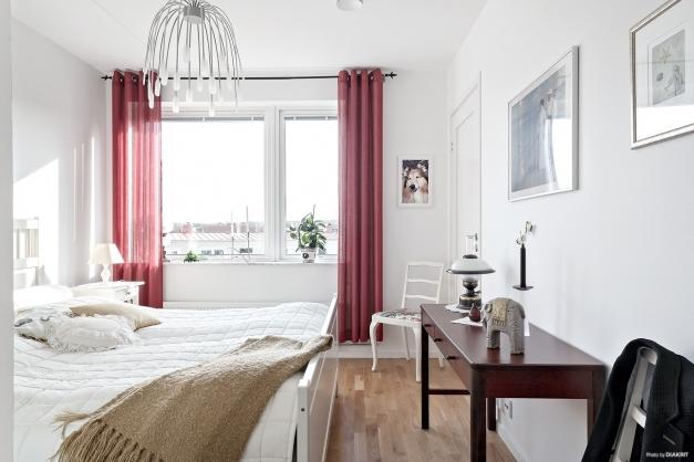 Stort sovrum med parkettgolv och tillhörande walk-in-closet med gott om utrymme för förvaring.