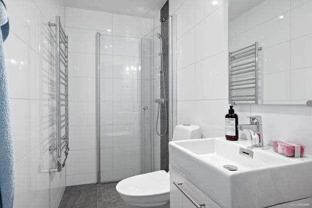 Helkaklad badrum med wc, handfat med kommod, handdukstork och dusch.