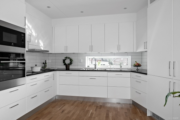 Välutrustat och stilrent kök i vitt med bra arbetsyta, indusktionshäll, fläkt, ugn med ång-funktion, micro, integrerad diskmaskin samt två integrerade kylar och frysar.