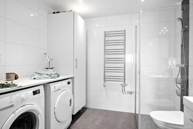Smakfullt helkaklat badrum med stora klinker och kakelplattor. Utrustat med dusch, wc, handfat med kommod, handdukstork, tvättmaskin och torktumlare samt en garderob.