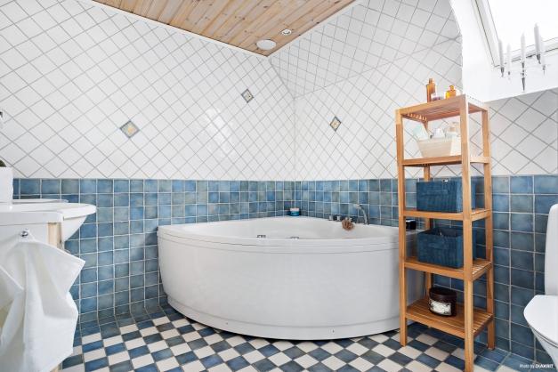 Helkaklat badrum med hörnbadkar på mellanvåningen