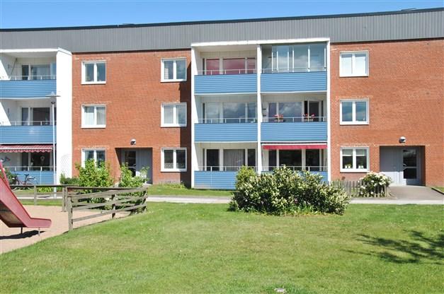 Fasadbild med lägenhetens balkong (den mittersta längst ned) och uteplats i västerläge (eftermiddags- och kvällssol)