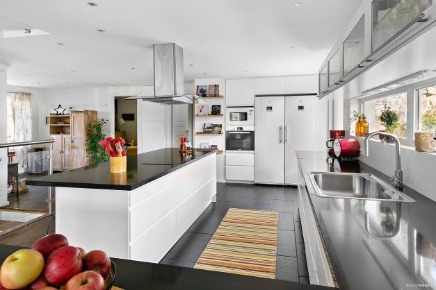 Ljust kök med gott om arbetsytor och bänkskiva i sten