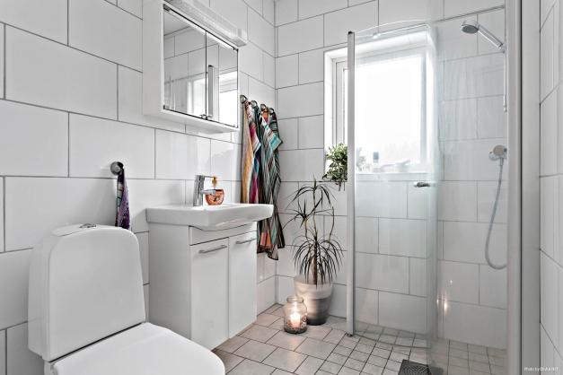 Stort badrum på nedre våning med toalett, vask och dusch.