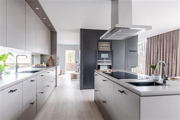 Köket är välplanerat med gott om förvaring och där allt går ton i ton i ljusgrått och svart.