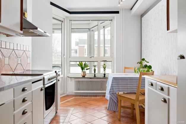 Kök med matplats och utgång till den stora inglasade balkongen
