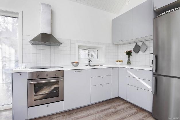 Kök med snickerier i vitt och maskiner i rostfritt