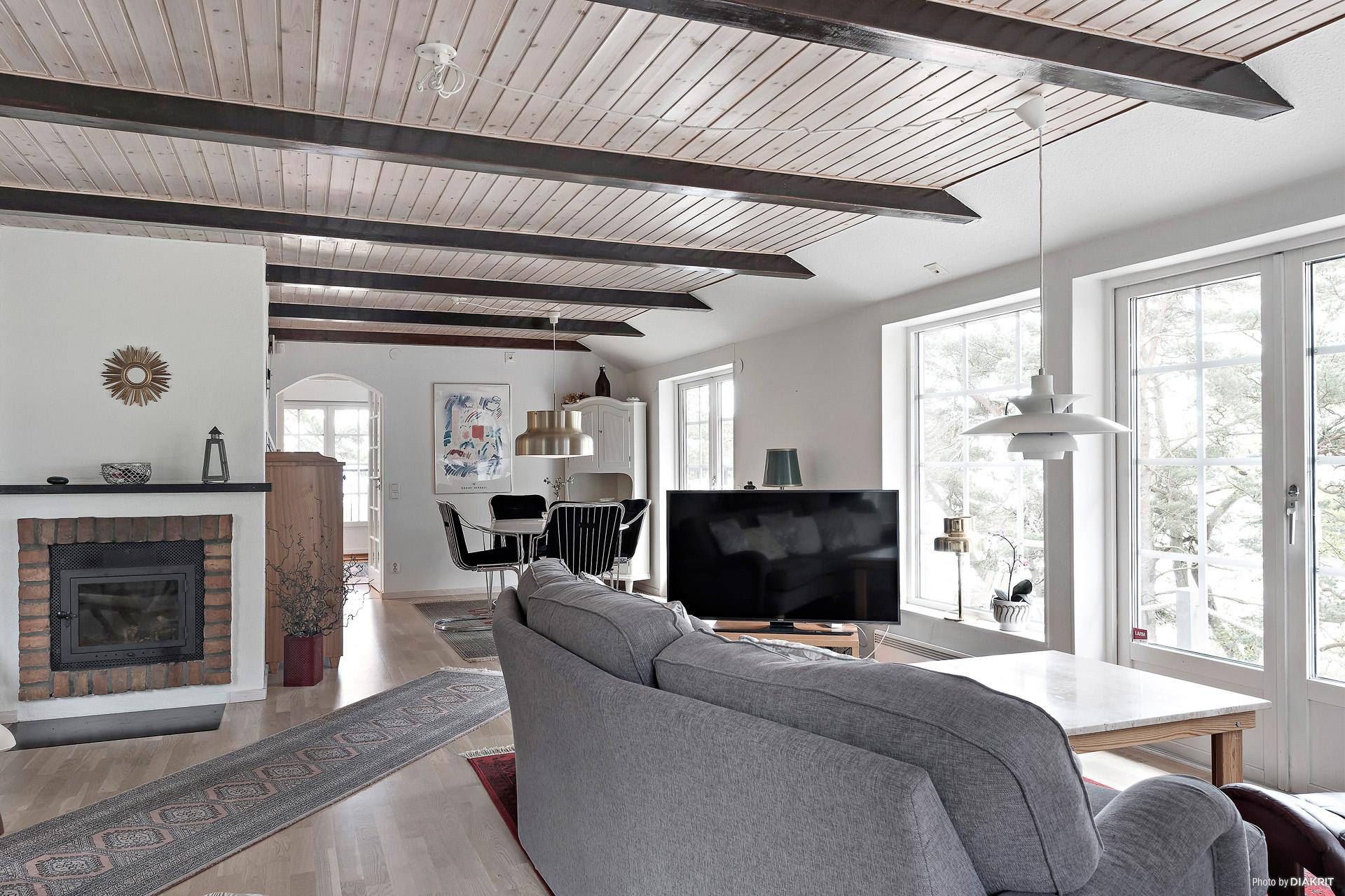 Vardagsrummet har öppenspis med braskasett som sprider skön värme i denna del av huset