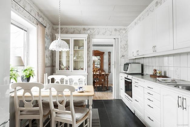 Ljust kök med plats för matbord vid fönster