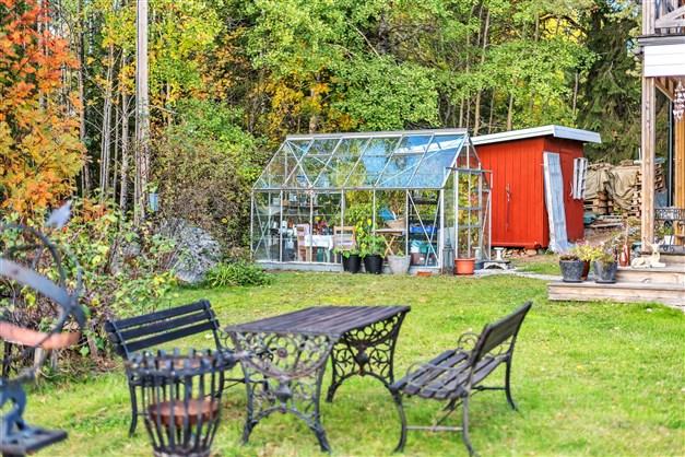 Trädgård med gräsytor, växthus och förråd/vedbod