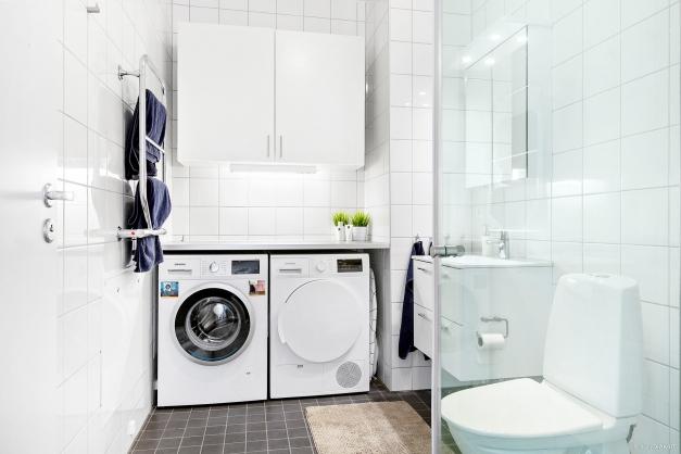 Helkaklat badrum med tvättmaskin/torktumlare.