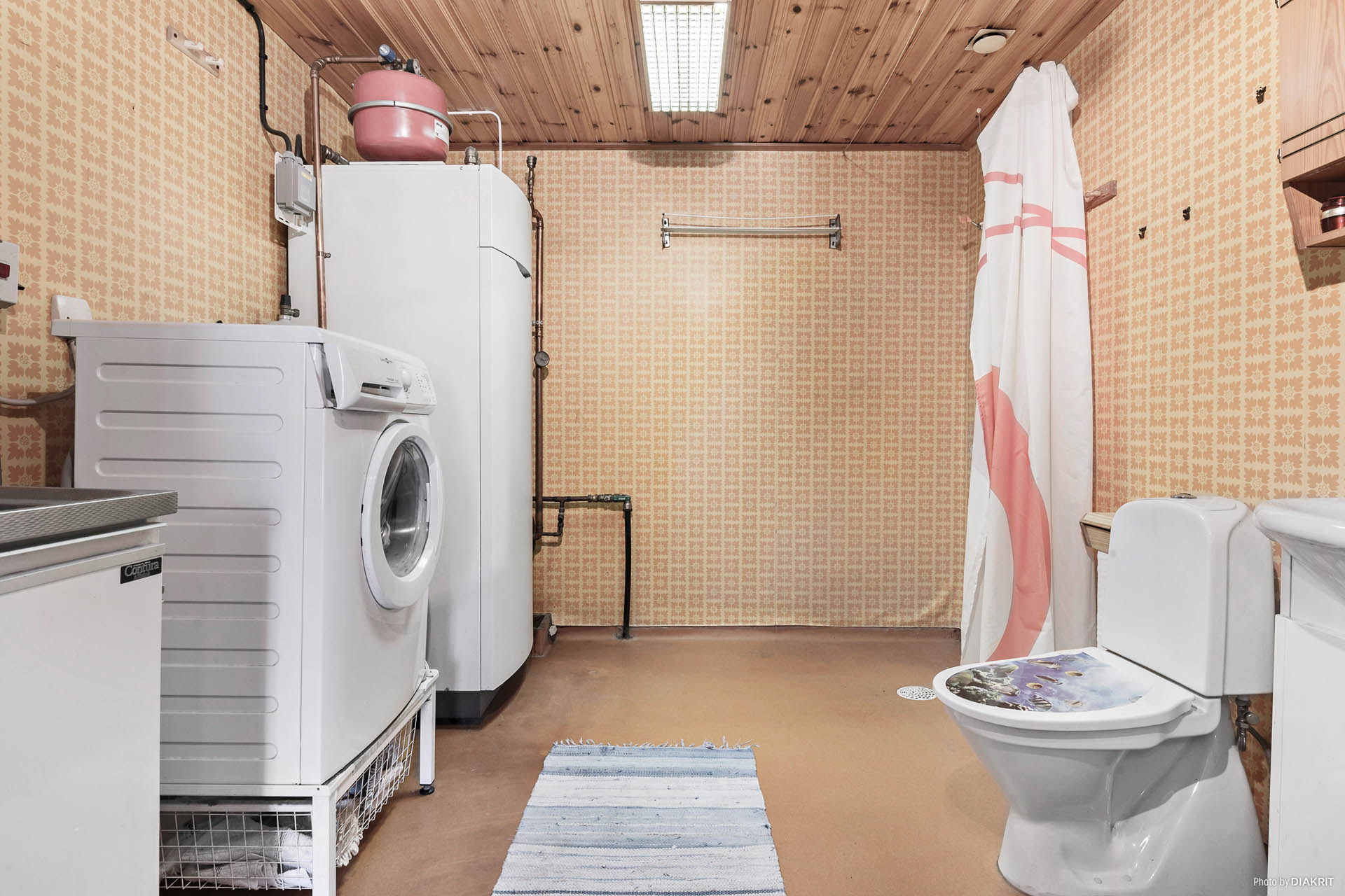 Badrum med  tvättmöjligheter. I badrummet finns även värmepumpen.