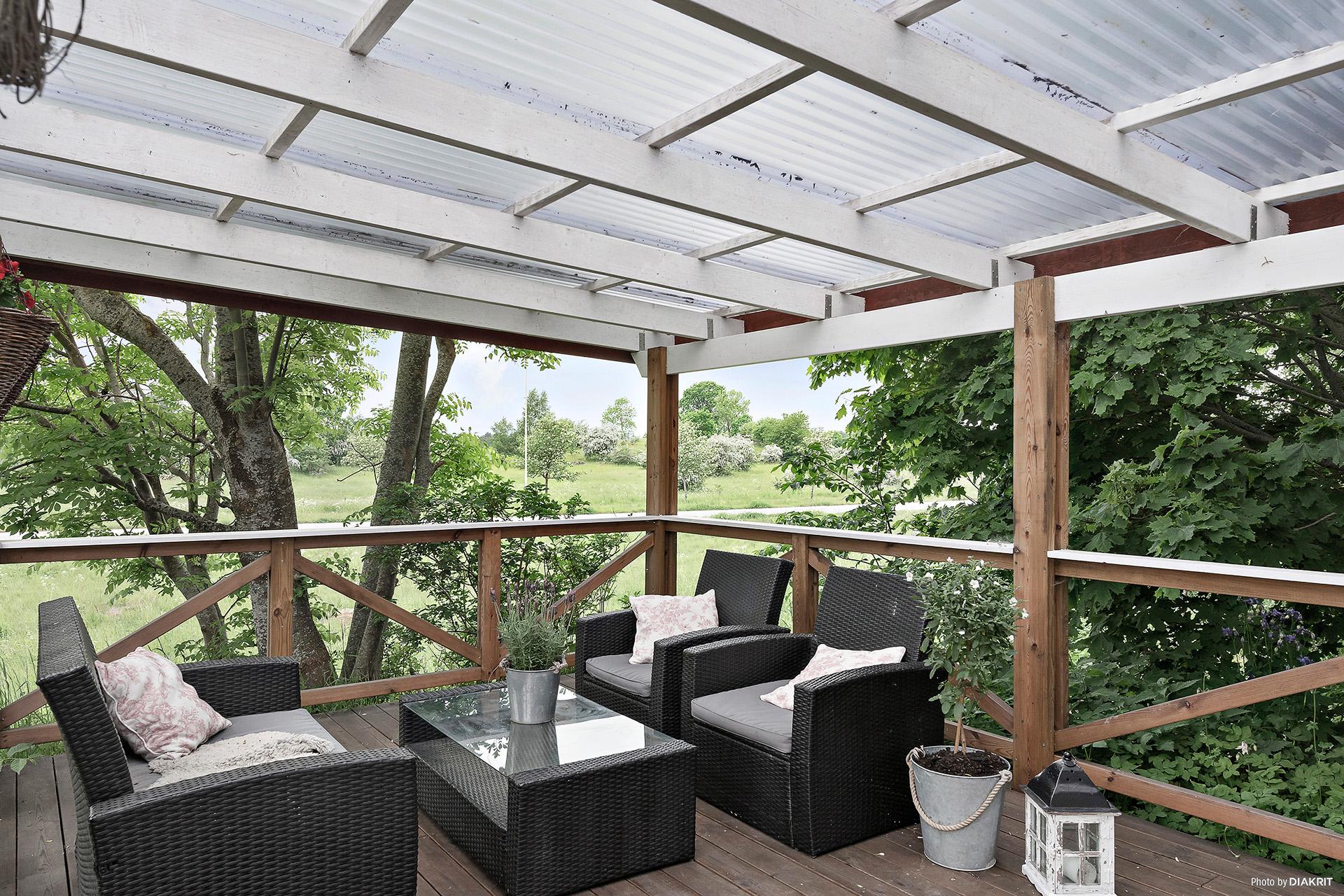 Överbyggd uteplats med grönska om sommaren. Här kan man sitta om regnet faller.