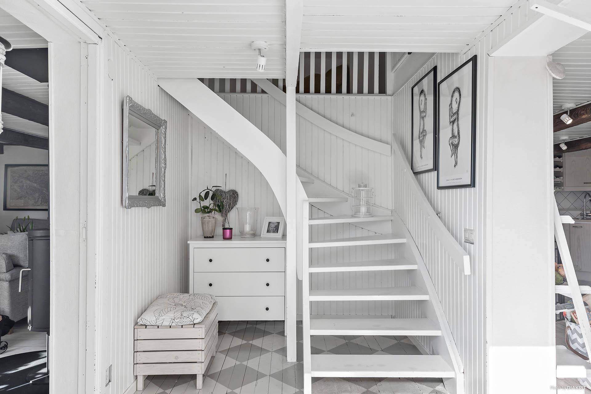 Söt hall med målat brädgolv i grå och vita rutor ger ett välkommet intryck. Här finner vi även trappan upp. Kök till höger och vardagsrum till vänster.
